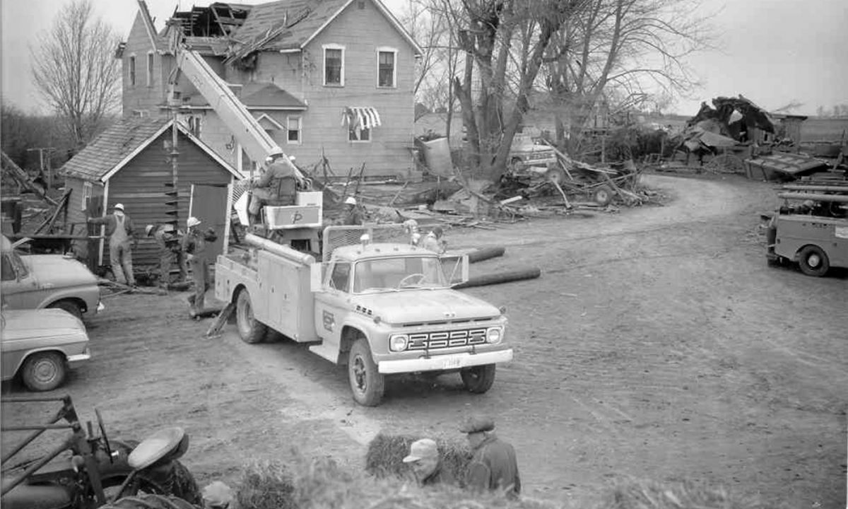 Black and white image of an older Eastern Iowa REC car in front of a house doing repairs